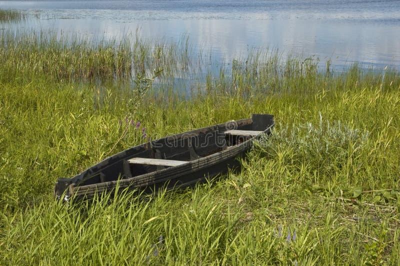 Oude houten boot op riverbank stock afbeelding