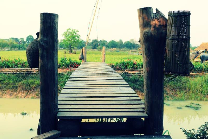 Oude houten brug die het landbouwdiekanaal kruisen met bamboe visserijhulpmiddelen bij cultureel park wordt verfraaid stock fotografie