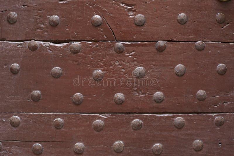 Oude houten bruine deur met de achtergrond van de spijkerstextuur stock foto