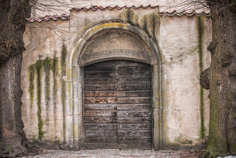 Oude houten deur in de oude muur van het steenkasteel stock foto's