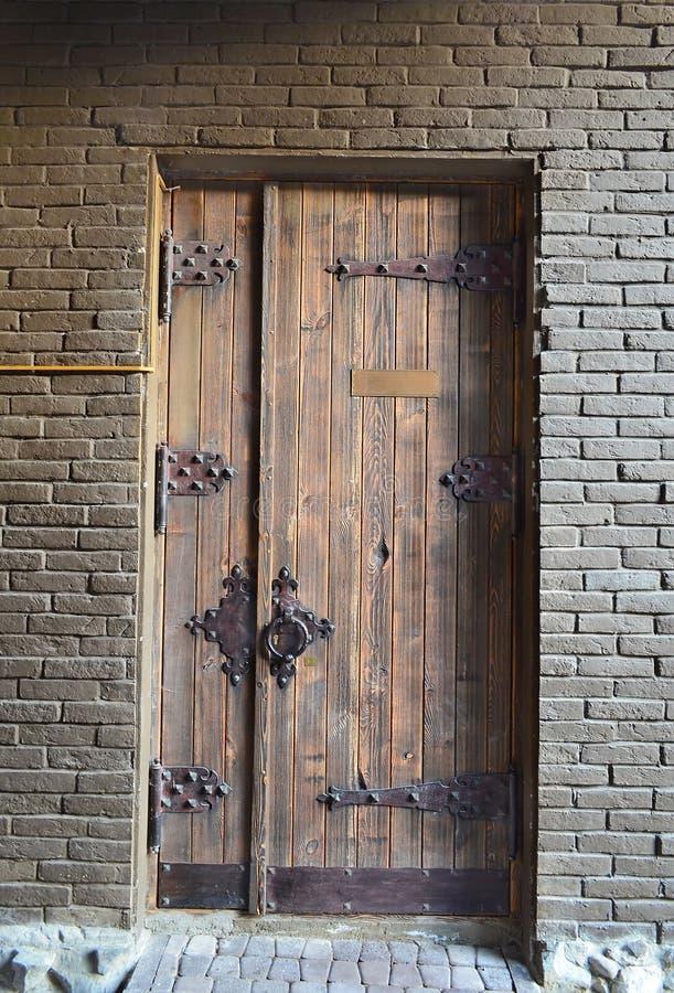 Oude houten deur in een bakstenen muur stock foto's