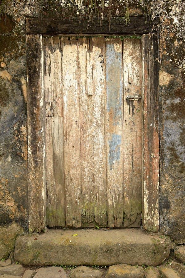 Oude houten deur in een oude muur stock fotografie