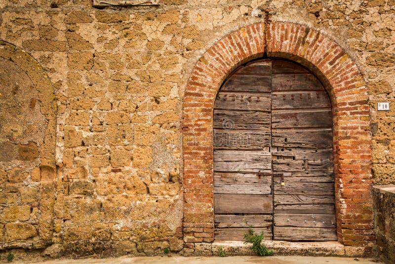 Oude houten deur en bakstenen muur stock afbeelding