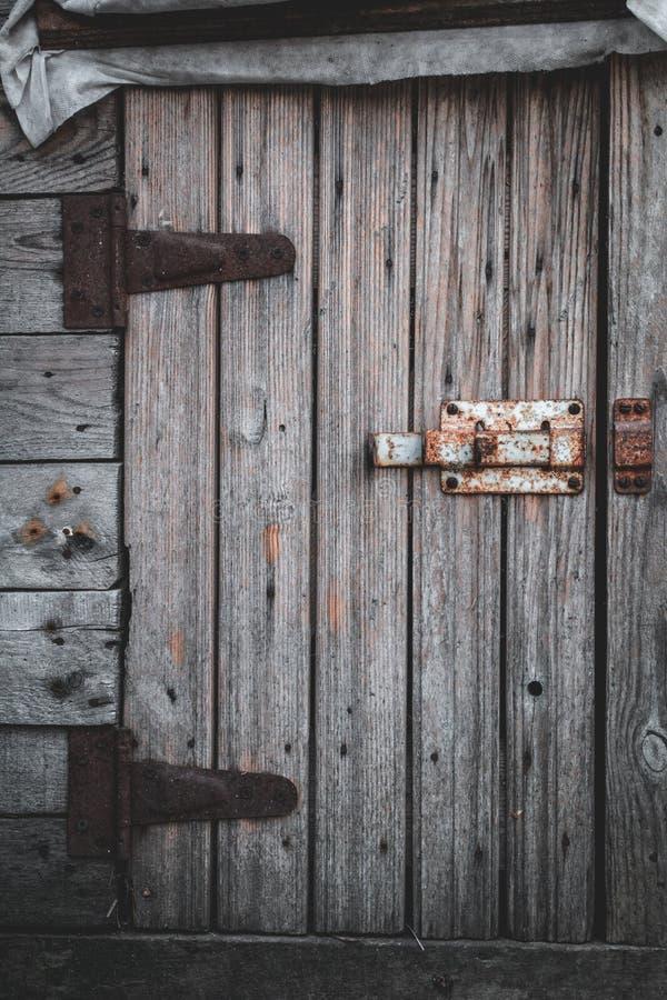 Oude houten deur en roestige deadbolt stock foto