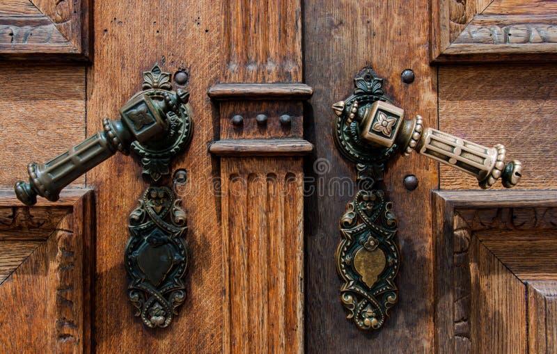 Oude houten deur met ijzerhandvatten stock afbeeldingen