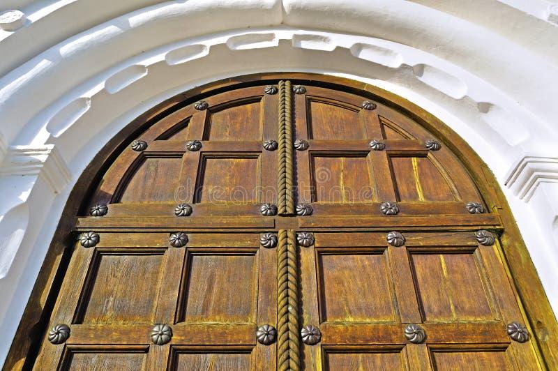 Oude houten deur met metaalklinknagels en boog van witte steen royalty-vrije stock afbeeldingen