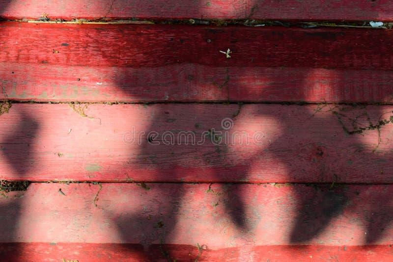 Oude houten die achtergrond van horizontale die raad wordt gemaakt, in rode verf, met schaduwen en zonlicht wordt geschilderd stock foto