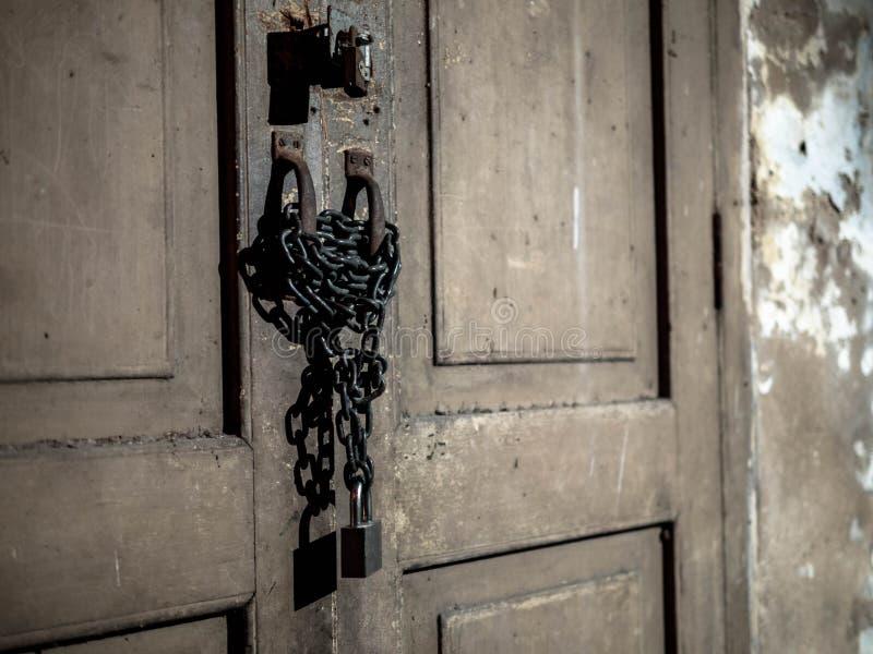 Oude houten die deur met roestig ketting en hangslot wordt gesloten stock afbeeldingen