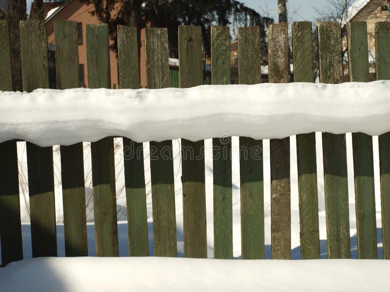 Oude houten die dorpsomheining met sneeuw wordt behandeld De sneeuwwinter in stock foto