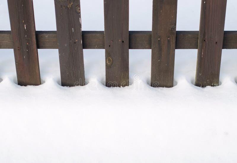 Oude houten die omheining door sneeuw wordt omringd Kerstmis en de winterconcept royalty-vrije stock afbeelding
