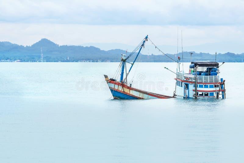 Oude houten die vissersbootschipbreuk in het overzees wordt ondergedompeld stock afbeelding
