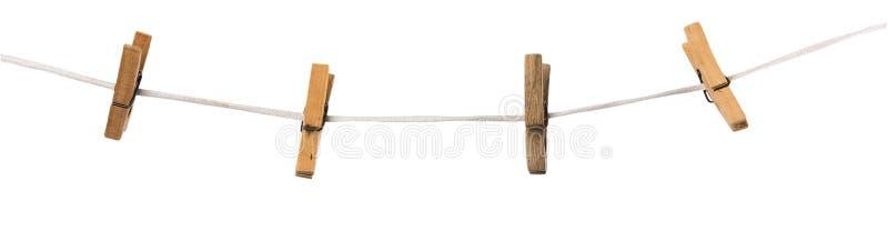 Oude houten die wasknijpers op een kabel op achtergrond wordt geïsoleerd stock fotografie