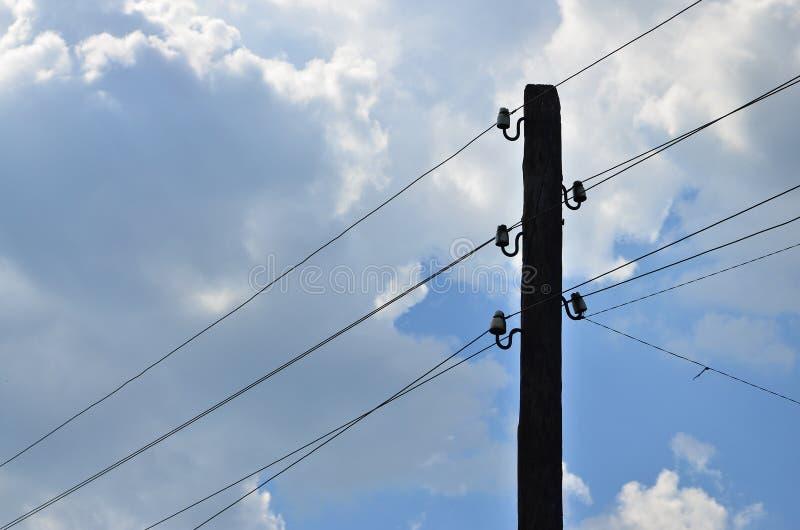 Oude houten elektrische pool voor transmissie van getelegrafeerde elektriciteit op een achtergrond van een bewolkte blauwe hemel  royalty-vrije stock foto