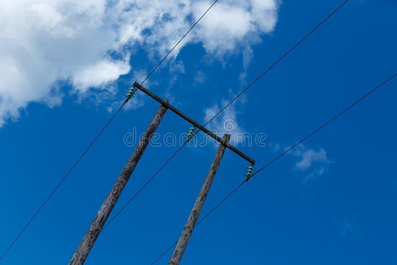 Oude houten elektrische post tegen blauwe hemel en wolken royalty-vrije stock foto