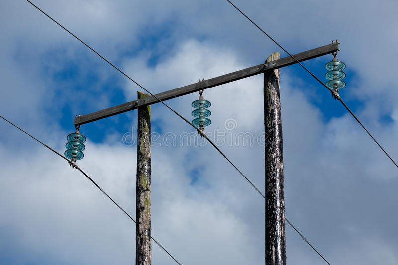 Oude houten elektrische post tegen blauwe hemel en wolken stock foto's