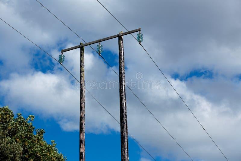 Oude houten elektrische post tegen blauwe hemel en wolken royalty-vrije stock afbeeldingen