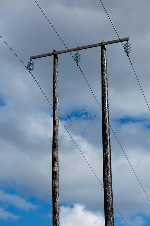 Oude houten elektrische post tegen blauwe hemel en wolken stock afbeelding