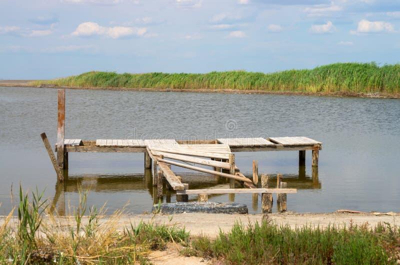 Oude houten geruïneerde pijler op de rivierbank stock afbeelding