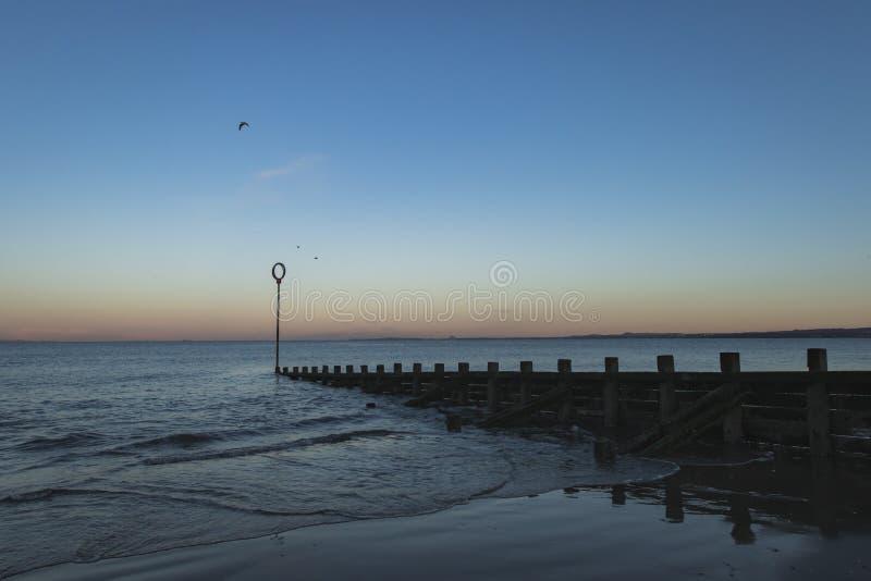 Oude houten Golfbreker op Portobello-strand bij zonsondergang stock foto