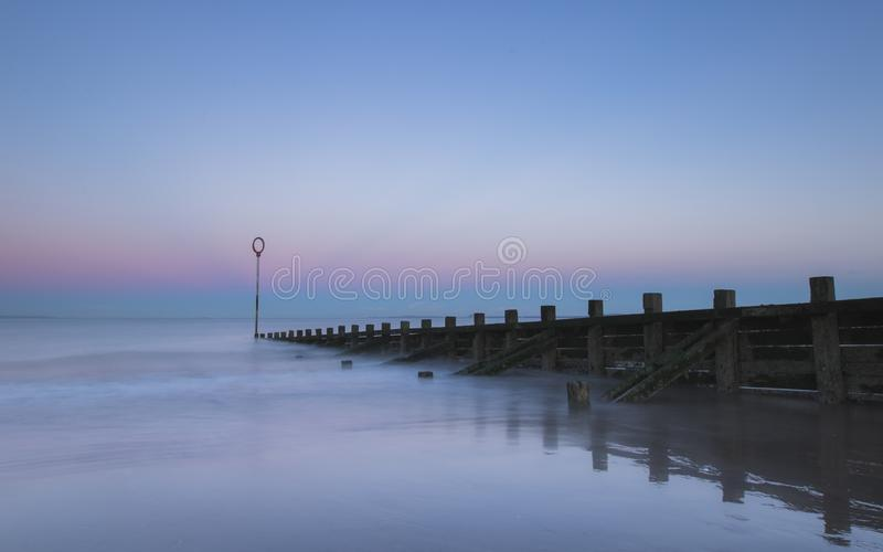 Oude houten Golfbreker op Portobello-strand bij zonsondergang stock foto's