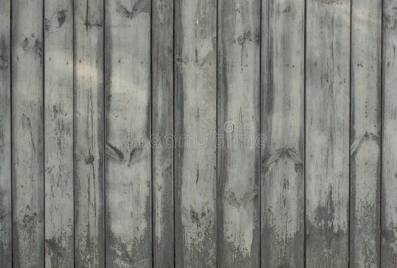 Oude houten grijze omheining voor achtergrond van raad van verschillende breedten stock fotografie