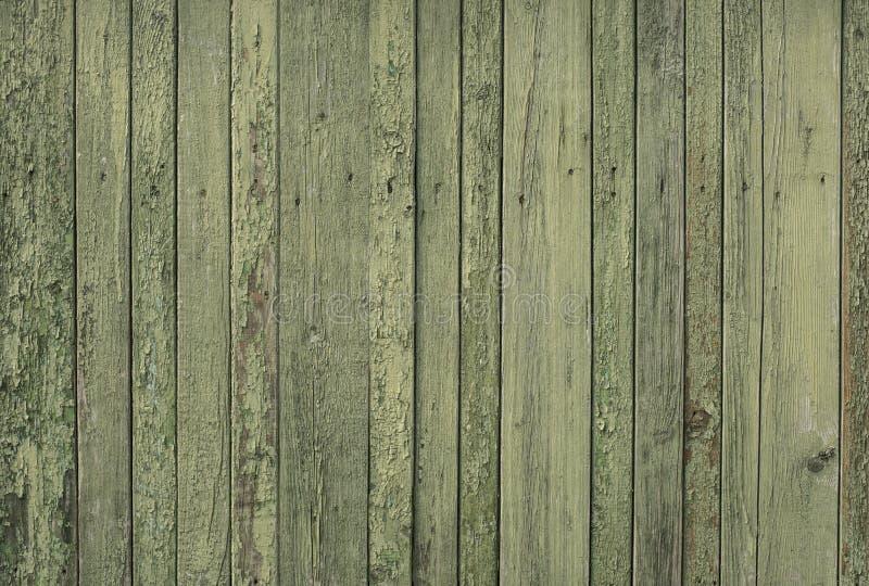 Oude houten groene omheining voor achtergrond van raad van verschillende breedten stock afbeelding