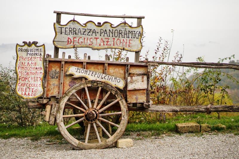 Oude houten kar dichtbij een proevende typische productenboerderij in Toscaans platteland van Montepulciano, Toscanië, Italië stock afbeelding
