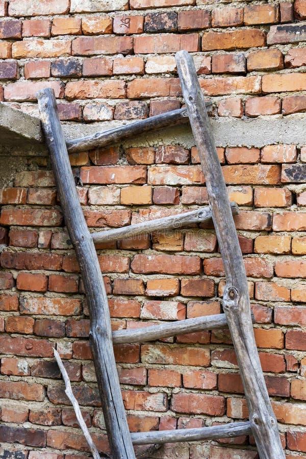 Oude houten ladder die tegen een niet beklede huisbakstenen muur leunen stock afbeelding