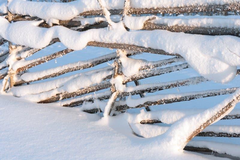 Oude houten omheining met sneeuw in de winter stock afbeeldingen