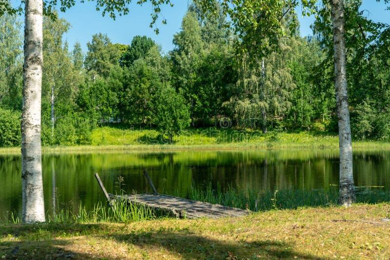 Oude houten pijler bij een klein meer op het Zweedse platteland stock afbeeldingen