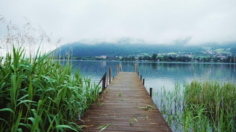 Oude houten pijler op een schilderachtig bergmeer in de Alpen in Oostenrijk Steaducamschot stock foto