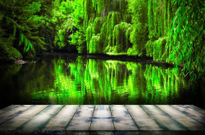 Oude houten plank in de voorgrond, pijler voor vissers op de achtergrond van een klein meer Het malplaatje kan worden gebruikt om stock foto