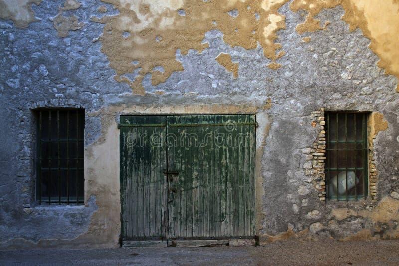 Oude houten poorten en twee raspende vensters stock afbeelding