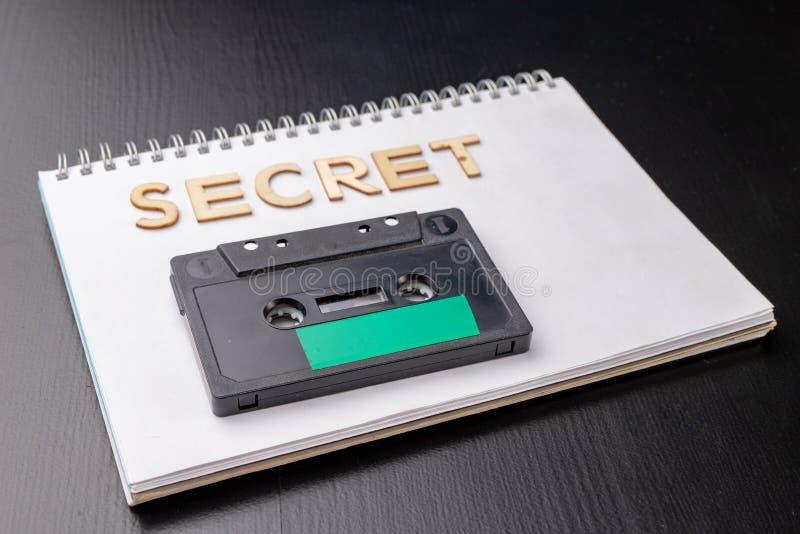 Oude houten rubberzegel en audiocassette op een wit stuk van notitieboekje Geheime opnamen van politieke besprekingen royalty-vrije stock foto