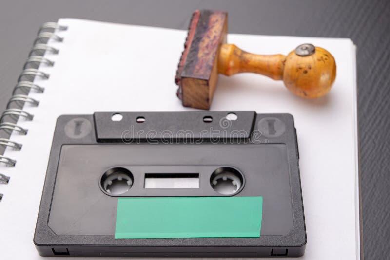 Oude houten rubberzegel en audiocassette op een wit stuk van notitieboekje Geheime opnamen van politieke besprekingen stock afbeeldingen