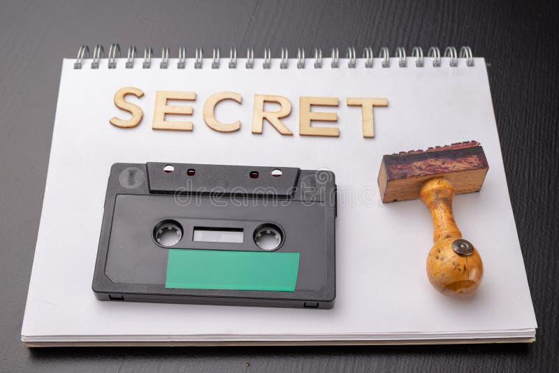 Oude houten rubberzegel en audiocassette op een wit stuk van notitieboekje Geheime opnamen van politieke besprekingen stock afbeelding
