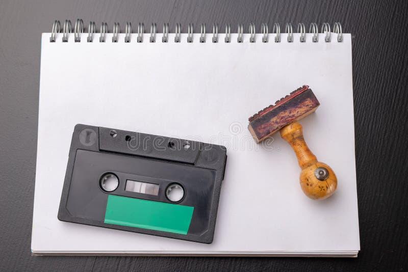 Oude houten rubberzegel en audiocassette op een wit stuk van notitieboekje Geheime opnamen van politieke besprekingen stock foto's