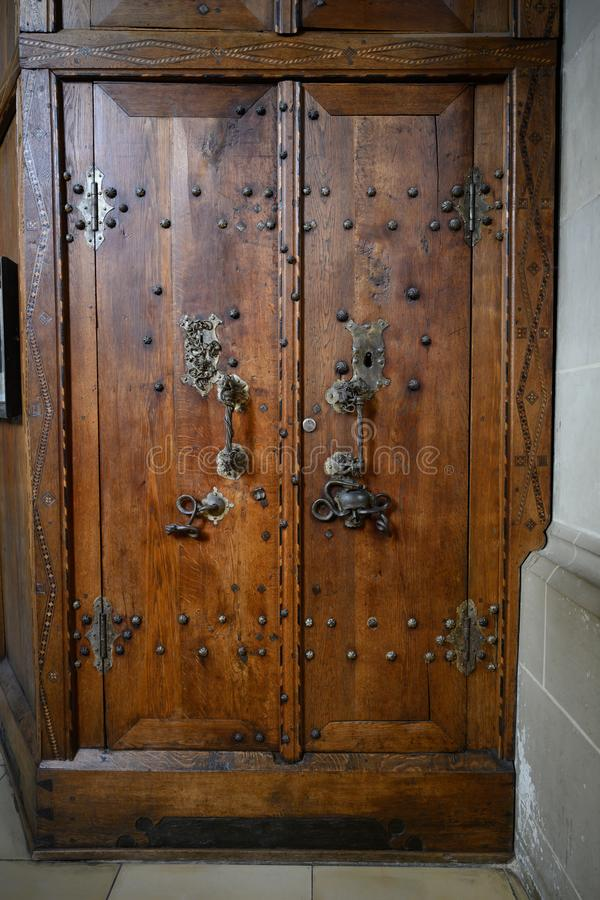 Oude houten sacristiedeur met schedel en slang op deursteun, Heilige Michael Church Schwabisch Hall, Duitsland stock foto's