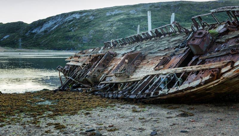 Oude houten verlaten schiptribunes op een zandig strand in mooi n stock fotografie