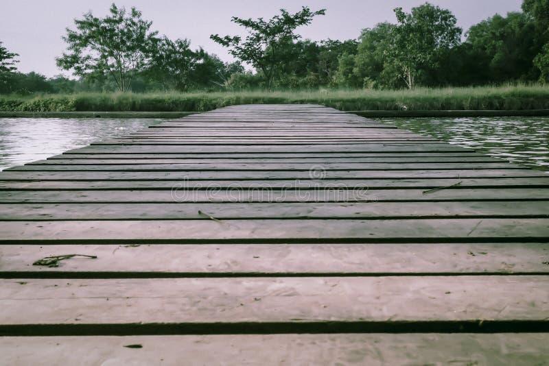Oude Houten Voetbrug met leuningen over het overzees het bewegen zich op conceptenidee stock foto