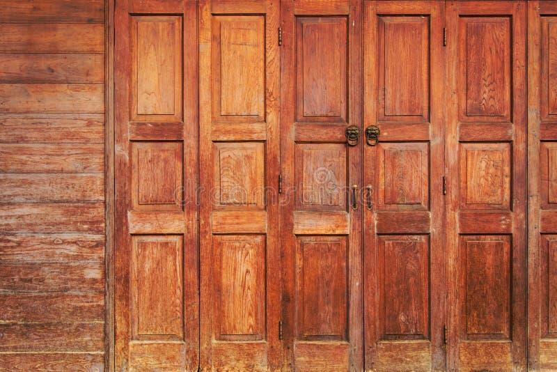 Oude houten vouwende deuren met handvat van de leeuw het hoofddeur De achtergrond van de kunst Het is mogelijk om in de projecten royalty-vrije stock foto