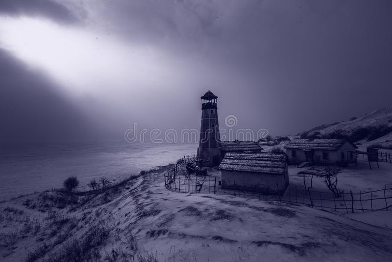 Oude houten vuurtoren in nacht bij rand van bevroren haven met bewolkte hemel Blauw atmosferisch licht stock afbeelding