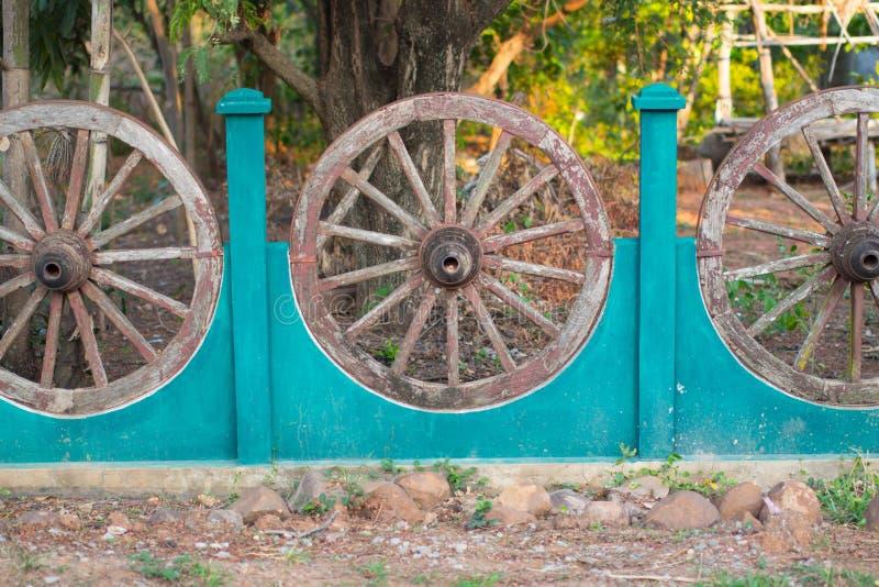 Oude houten wagenwielen in een muur in Thailand stock fotografie