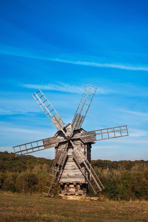 Oude houten windmolen op de heuvel stock afbeelding