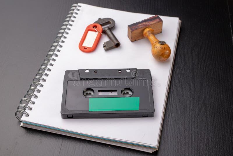 Oude houten zegel en een cassetteband op een wit stuk van notitieboekje Een sleutel tot geheime opnamen van politieke besprekinge royalty-vrije stock afbeelding