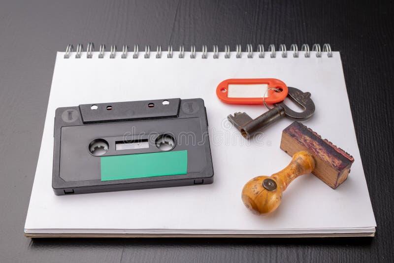 Oude houten zegel en een cassetteband op een wit stuk van notitieboekje Een sleutel tot geheime opnamen van politieke besprekinge stock foto