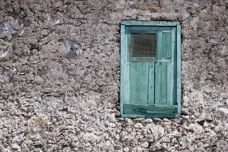 Oude huisvoorgevel met houten venster en gesloten blind stock fotografie
