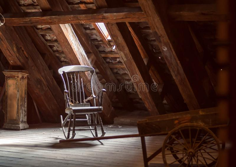 Oude huiszolder met retro meubilair, houten schommelstoel Verlaten huisconcept stock foto