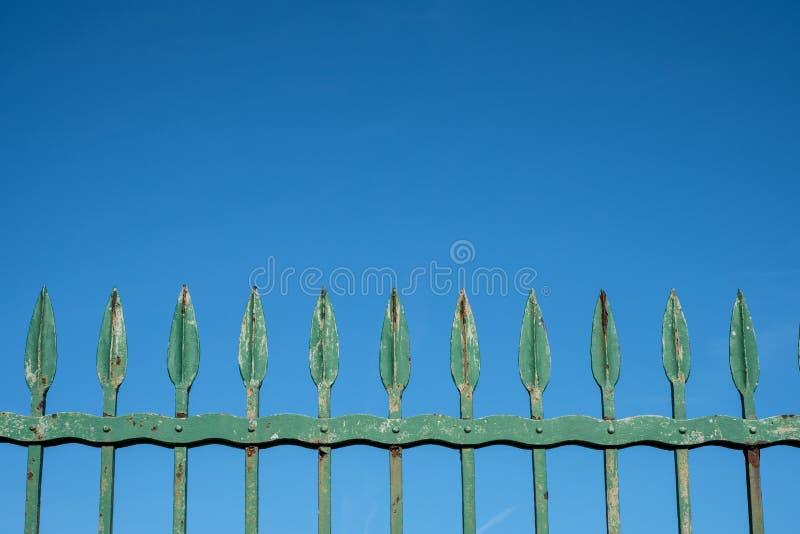 Oude ijzeromheining op blauwe hemel - uitstekende vervaardigde metaalaren - royalty-vrije stock fotografie