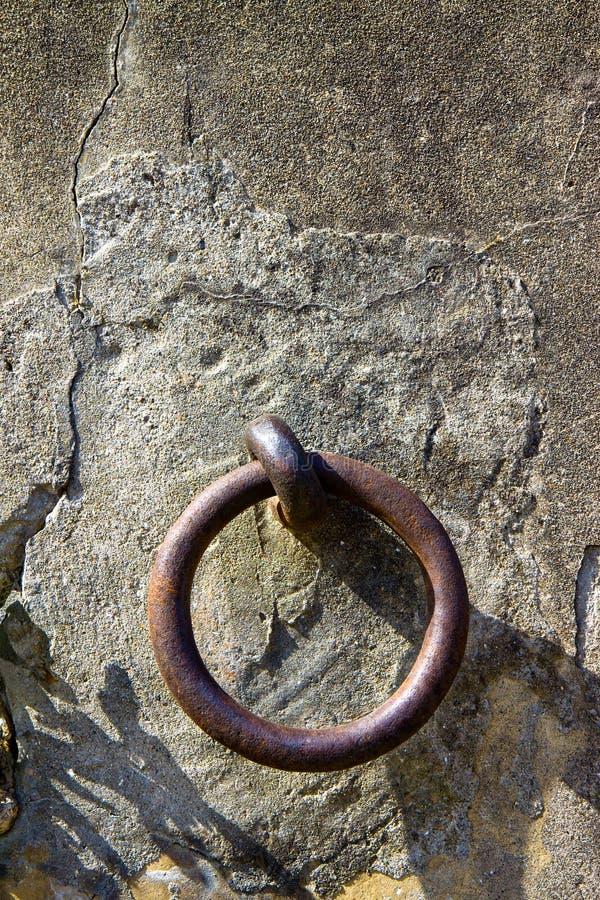 Oude ijzerring vast in een pleistermuur stock fotografie